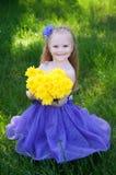 Een jong meisje op een groen gras Stock Afbeeldingen
