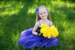 Een jong meisje op een groen gras Stock Afbeelding