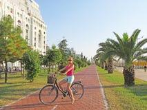 Een jong meisje op een fiets berijdt langs de waterkant Ci stock foto