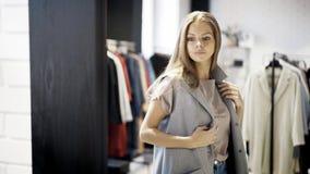 Een jong meisje probeert op een grijs jasje in een winkel stock fotografie