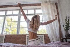 Een jong meisje rekt zich terwijl ontwakenzitting op bed met rug vroeg bekijkend het venster in de ochtend in moderne slaapkamer  Stock Foto