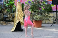 Een jong meisje in roze danst Het glimlachen het dansen Het dansen in de straat Bij kostuum het dansen royalty-vrije stock afbeelding