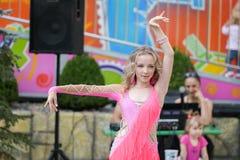Een jong meisje in roze danst Het glimlachen het dansen Het dansen in de straat Bij kostuum het dansen royalty-vrije stock foto