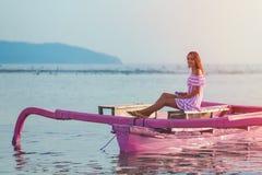Een jong meisje in roze sundress die in een kleine boot op kalm water, bij zonsondergang rusten stock afbeelding