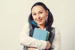 Een jong meisje is een student van een middelbare schoolstudent met een stapel handboeken in haar handen Op witte achtergrond royalty-vrije stock foto's