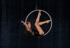 Een jong meisje voert de acrobatische elementen in de luchthoepel uit Zwarte Aqua Studio stock afbeeldingen