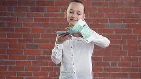 Een jong meisje werpt geld met haar handen stock video