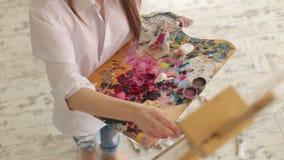 Een jong meisje in een wit overhemd trekt op canvas in de studio Art stock footage
