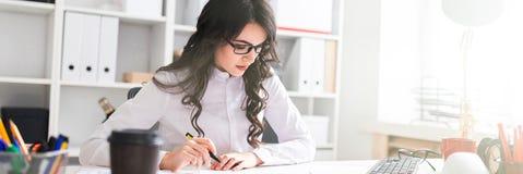 Een jong meisje zit bij de bureaulijst, houdt een pen in haar hand en bekijkt de documenten royalty-vrije stock fotografie
