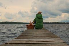 Een jong meisje zit op de rand van een houten pijler en onderzoekt de afstand Volyngebied ukraine Stock Fotografie