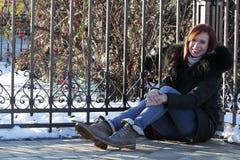 Een jong meisje zit op de vloer, in aard, in een halve draai het houden van zijn knieën met zijn handen, het glimlachen en het be stock foto
