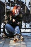 Een jong meisje zit op de vloer, trekt haar handschoen en lach, weg kijkend op een zonnige de winterdag uit royalty-vrije stock afbeelding