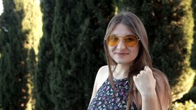 Een jong meisje in zonnig de zomerweer loopt in het park lopend langs het groene straat stellen voor de camera stock footage