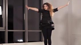 Een jong meisje in een zwarte kleding die dans repeteren, de dame is bezig geweest met moderne stijl Energie, zaal, venster, dans stock footage