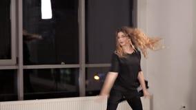 Een jong meisje in een zwarte kleding die dans repeteren, de dame is bezig geweest met moderne stijl Energie, zaal, venster, dans stock video