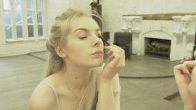 Een jong mooi blonde kijkt in een grote spiegel en past make-up op haar gezicht toe Hij bewondert zich in een grote ruimte met stock footage