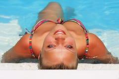 Een jong mooi meisje is in blauwe woter Stock Foto's
