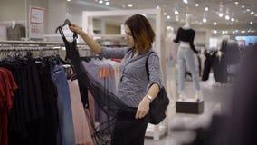 Een jong, mooi meisje in een supermarkt kiest kleren Het meisje ging in de boutique een nieuwe garderobe vinden stock video