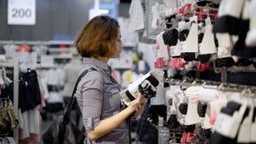 Een jong, mooi meisje in een supermarkt kiest kleren Het meisje ging in de boutique een nieuwe garderobe vinden stock videobeelden