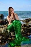 Een jong mooi meisje in een groen meerminkostuum zit op een steen op het strand tegen de hemel, koesterend haar hals met haar han royalty-vrije stock afbeeldingen