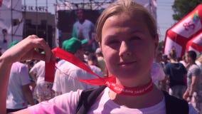 Een jong, mooi meisje in Holi-verf, na het runnen van een marathon, houdt een transparante medaille van Zaporizhstal 2018 bij stock footage