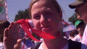 Een jong, mooi meisje in Holi-verf, na het runnen van een marathon, houdt een transparante medaille van Zaporizhstal 2018 bij stock video