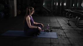 Een jong mooi meisje kneedt haar hoofd en hals vóór oefeningen in de gymnastiek Het zitten op de vloer en actief het doen van cir stock videobeelden