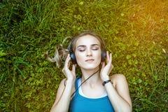 Een jong, mooi meisje luistert aan een acdbook met hoofdtelefoons P Royalty-vrije Stock Foto