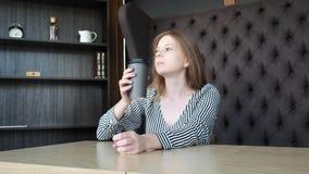 Een jong mooi meisje in een modieuze koffie drinkt koffie in de ochtend vóór het werk Zit tegenover het venster Hij drinkt stock footage