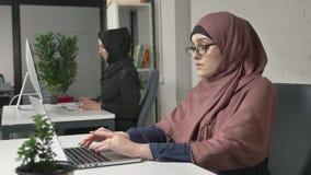 Een jong mooi meisje in roze hijab stijgt haar glazen op en masseert de brug van haar neus Vermoeide ogen Arabische meisjes stock footage