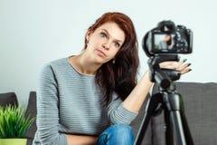 Een jong mooi meisje zit voor een DSLR en registreert een Vlog, close-up Blogger, het blogging, technologie, online geld, stock afbeeldingen