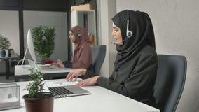Een jong mooi meisje in een zwarte hijab spreekt op de hoofdtelefoon, beantwoordend vraag in call centre Arabische vrouwen in stock video