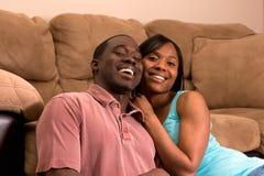 Een jong Paar dat samen door een Bank lacht Stock Afbeelding
