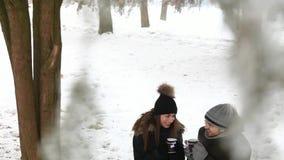 Een jong paar in de sprookjewinter wordt verwarmd door een warme drank stock videobeelden