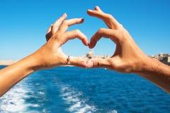 Een jong paar die hart maken met dient ringen, symbool van in liefde van de boot bij mooie mening over Valletta, Malta Stock Fotografie