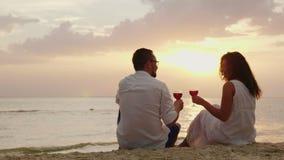 Een jong paar drinkt wijn door het overzees bij zonsondergang Zij zitten op het zand, gerinkelglazen Verjaardag of wittebroodswek stock footage