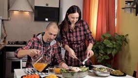 Een jong paar gemaakt tot diner, salades, groenten, een jong meisje snijdt een gebraden kip, giet een jonge kale kerel sap in a stock video