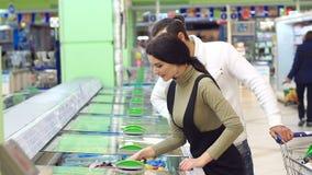Een jong paar koopt bevroren bessen in een supermarkt die zich dichtbij een ijskast bevinden stock video