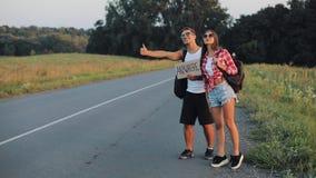 Een jong paar lift status op de weg Een man en een vrouw houden de auto overal op de weg met een teken tegen stock footage