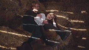 Een jong paar ligt koesterend hooi in de schuur De gelukkige glimlachende jongen en het meisje brengen samen tijd door Langzame M stock footage