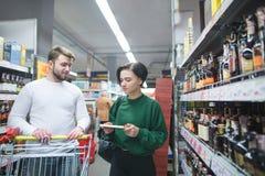 Een jong paar loopt door de alcoholafdeling van een supermarkt en maakt aankopen Het winkelen bij een supermarkt royalty-vrije stock foto