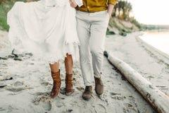 Een jong paar loopt op de overzeese kustlijn Close-upbeeld van benen kunstwerk Stock Foto's