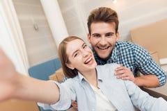 Een jong paar maakt selfie terwijl zich het bewegen aan een nieuwe flat Bewegende jonggehuwden aan nieuwe huisvesting stock afbeeldingen