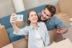 Een jong paar maakt selfie terwijl zich het bewegen aan een nieuwe flat Bewegende jonggehuwden aan nieuwe huisvesting royalty-vrije stock foto's