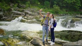 Een jong paar van reizigers die fotograferen tegen de achtergrond van een waterval in de bergen Kraanschot stock video