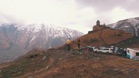 Een jong paar van reizigers heft zijn wapens op de achtergrond van bergen op stock videobeelden