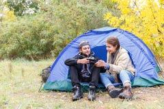 Een jong paar van toeristen in de bos het letten op foto's op de camera stock afbeeldingen