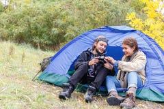 Een jong paar van toeristen in de bos het letten op foto's op de camera stock fotografie