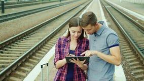 Een jong paar van toeristen gebruikt een tablet bij het station Kaartje online, het begin van een goede vakantie stock footage