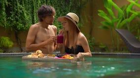Een jong paar van wittebroodswekentoeristen heeft hun eigen persoonlijk ontbijt op een drijvende lijst in een privé zwembad stock videobeelden